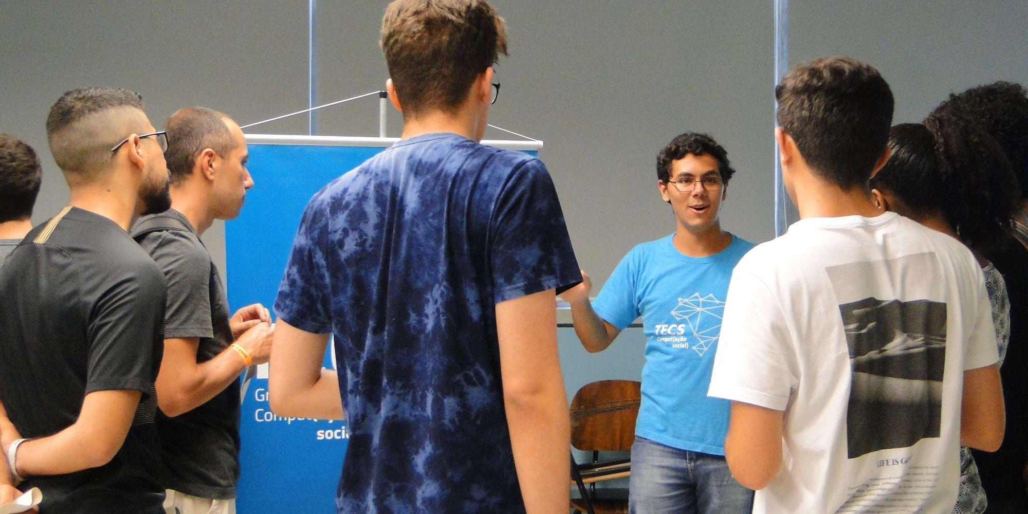 6 pessoas reunidas em volta de um integrante do Tecs (com a camiseta do grupo) apresentando o grupo em um evento de recepção de bixes em uma sala do IME-USP.