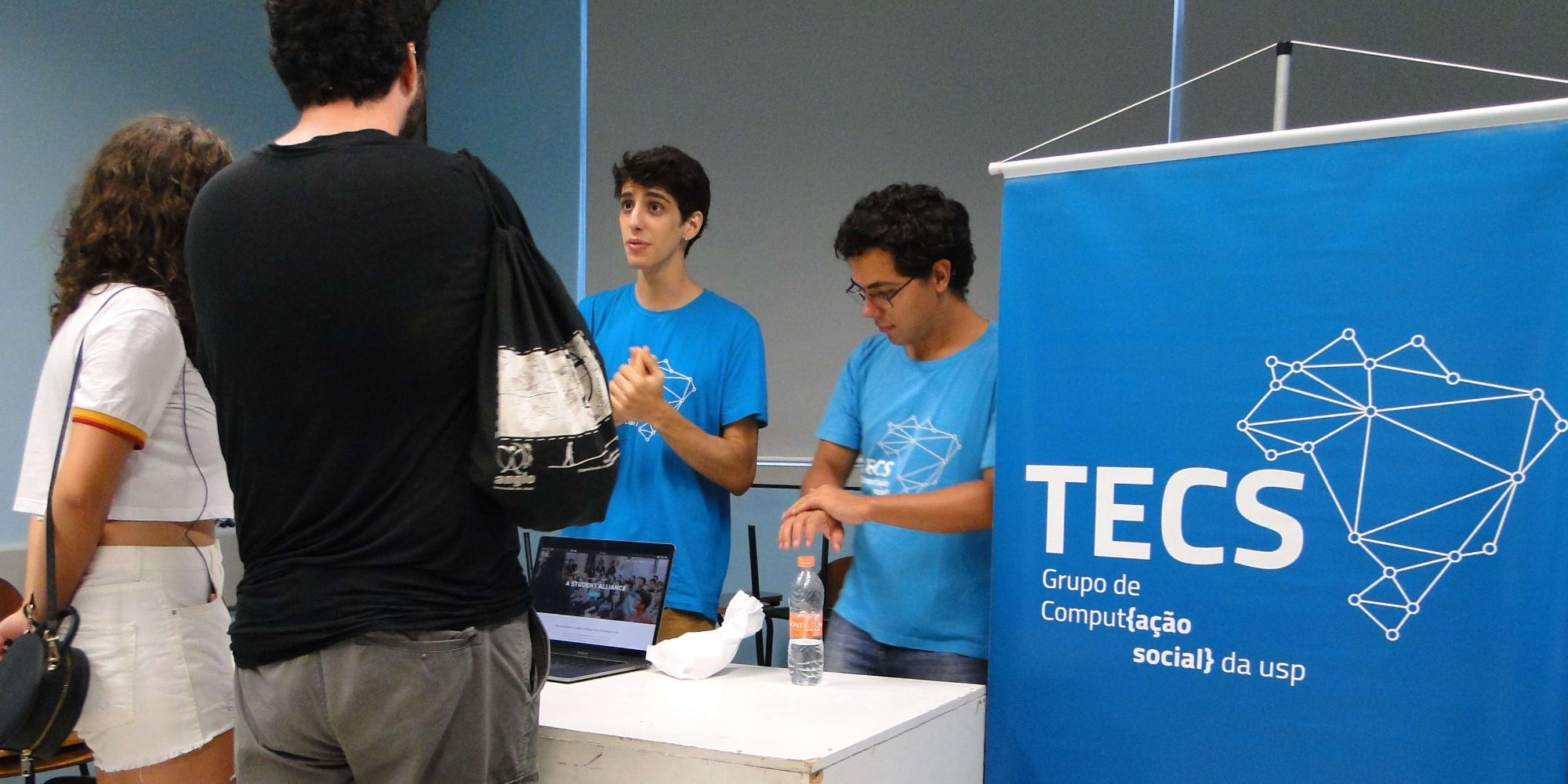 Dois integrantes do Tecs (com a camiseta do grupo) apresentam o grupo para duas pessoas. Entre os dois grupos, há uma mesa e um 'banner' do Tecs.