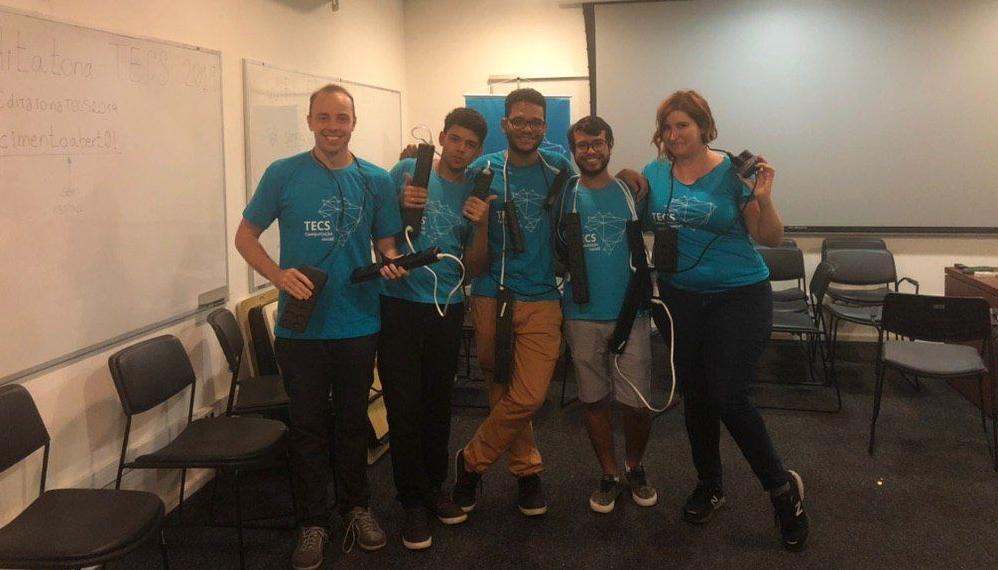 5 integrantes do Tecs (vestindo a camisa do grupo) em um auditório do IME-USP brincando com extensões elétricas, em um trocadilho com extensão universitária