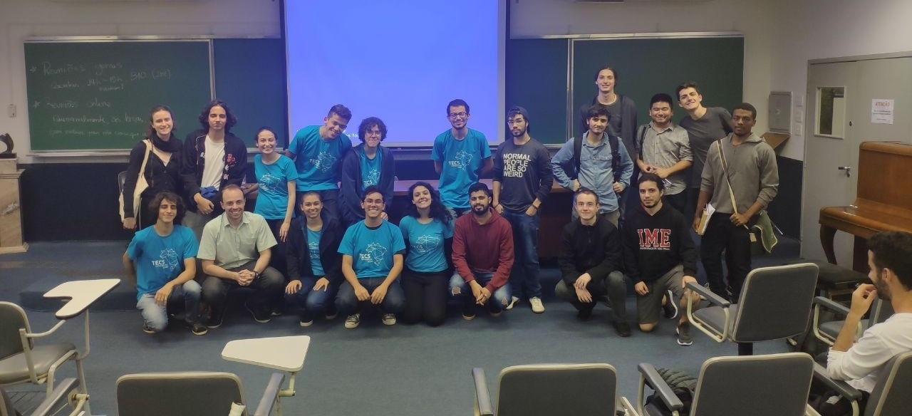 Em 2 fileiras, integrantes do Tecs (vestindo a camiseta do grupo) e participantes do EnconTecs em um auditório do IME-USP. Ao total, 18 pessoas na frente de uma tela de projetor.