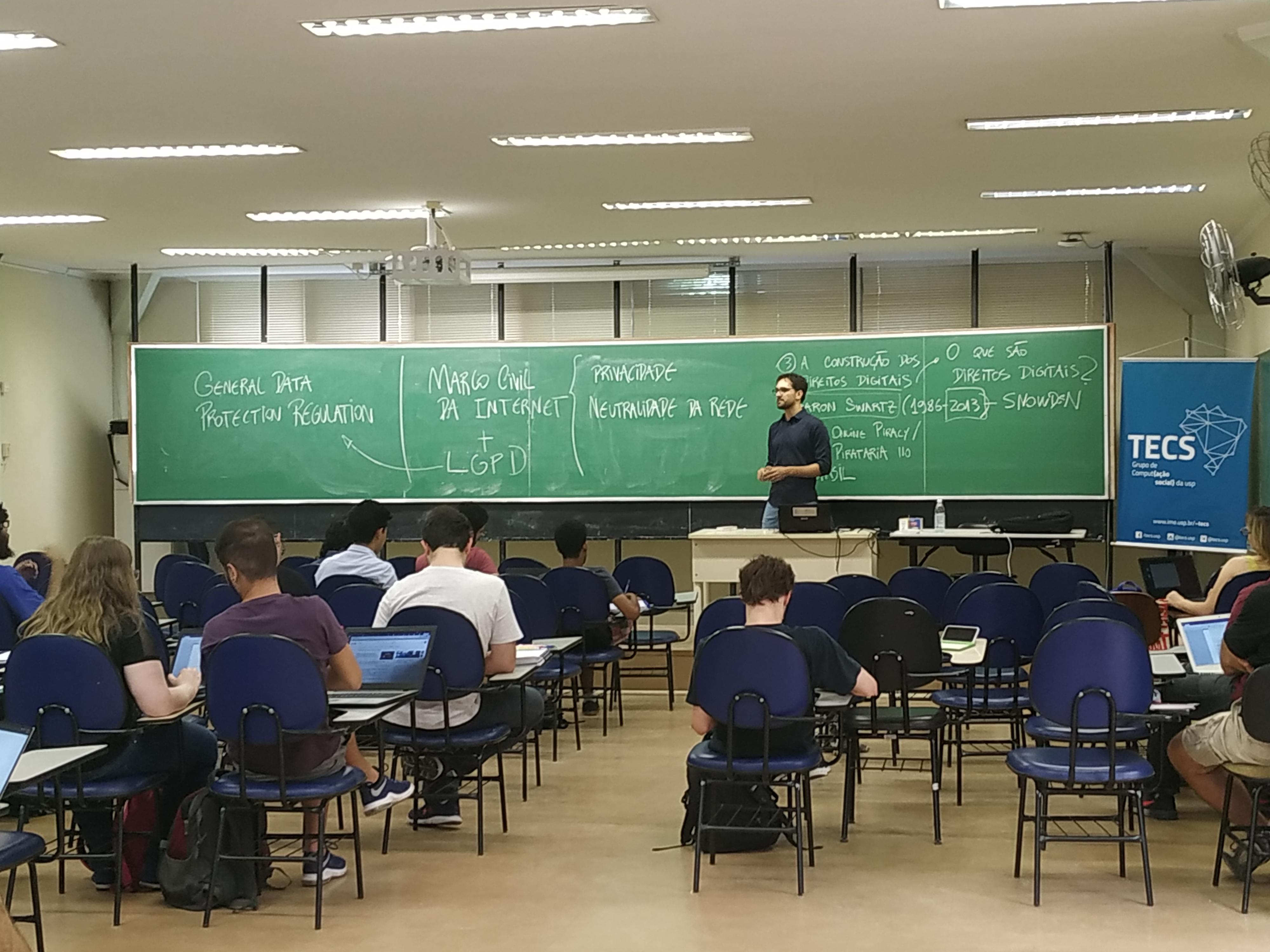 Professor voltado para o canto esquerdo da sala, de frente para estudantes que fazem anotações em cadernos e laptops. Ao fundo, uma larga lousa de giz com esquemas explicativos.